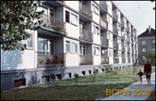 Osiedle mieszkaniowe Prototypów na Służewcu, kobieta z dzieckiem spacerująca chodnikiem obok czterokondygnacyjnego budynku mieszkalnego, Warszawa