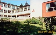 Szkoła podstawowa, widok zewnętrzny z widocznym na elewacji godłem i tablicą szkoły, łącznikiem oraz terenem zielonym, Gdańsk-Wrzeszcz