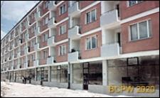 Widok pięciokondygnacyjnego długiego bloku mieszkalnego z niezagospodarowaną zabudową na parterze, Poznań