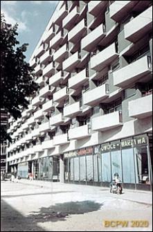 Plac Waryńskiego, niedaleko pętli tramwajowej, ośmiopiętrowy blok o trapezowych balkonach i pawilonach handlowo-usługowych na parterze, Poznań