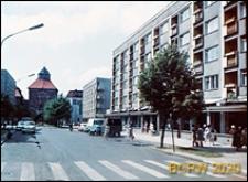 Ulica Nowobramska, dawniej gen. Zawadzkiego, bloki z parterową zabudową handlowo-usługową, w głębi widoczna Nowa Brama, Słupsk