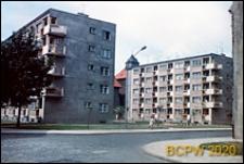 Nowa Brama, fragment budynku i pięciokondygnacyjne bloki mieszkalne z zielonymi terenami międzyblokowymi, Słupsk